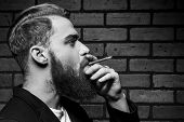 picture of macho man  - Black and white portrait of handsome young bearded man smoking a cigarette while standing against brick wall - JPG