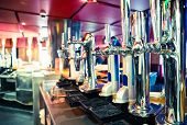 picture of tapping  - Shiny beer taps in a row in a bar - JPG
