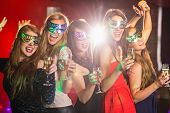 stock photo of masquerade mask  - Friends in masquerade masks drinking champagne at the nightclub - JPG