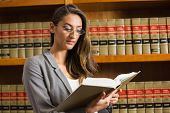 stock photo of laws-of-attraction  - Pretty lawyer reading in the law library at the university - JPG