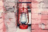 image of kerosene lamp  - Kerosene lamp on ruined brick wall background - JPG