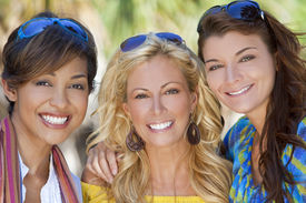 foto of beautiful young woman  - Three beautiful young women in their twenties laughing and having fun on vacation shot in golden sunshine in a tropical resort location - JPG