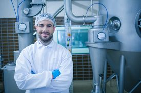 stock photo of food plant  - Food technician smiling at camera in a food processing plant - JPG