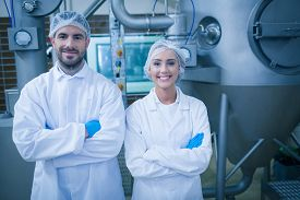picture of food plant  - Food technicians smiling at camera in a food processing plant - JPG