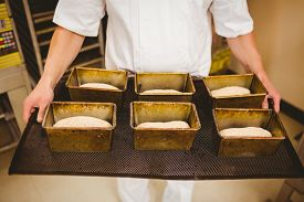 image of tin man  - Baker holding tray of loaf tins in a commercial kitchen - JPG