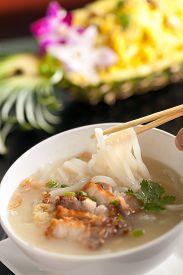 image of crispy rice  - Closeup of a person eating Thai style crispy pork rice noodle soup from a bowl with chopsticks - JPG