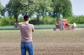stock photo of hoe  - Rear view of attractive farmer carrying hoe on shoulders in corn field in spring tractor in background - JPG