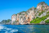 picture of phi phi  - Cliff and the clear sea with a boat near Phi Phi island in south of Thailand - JPG