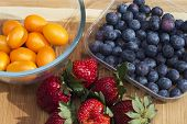 picture of kumquat  - Kumquat, strawberries and blueberries on a cutting board ** Note: Visible grain at 100%, best at smaller sizes - JPG