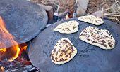 stock photo of pita  - Pita bread baking on a Saj or Tava on Lag Baomer - JPG