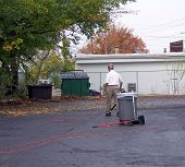 pic of leaf-blower  - man with leaf blower at store parking lot - JPG