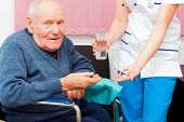 picture of kindness  - Elderly man in wheelchair taking several medications from kind nurse - JPG