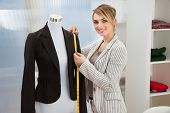 stock photo of measurements  - Portrait Of Fashion Designer Measuring Suit With Measuring Tape - JPG
