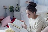 foto of short-story  - Young attractive woman leafing through favorite book - JPG