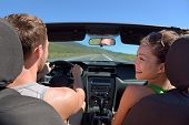 stock photo of steers  - Couple driving car on road trip travel vacation in convertible - JPG