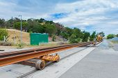 picture of railroad yard  - Multiple rails wait for installation on a train track - JPG