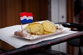 picture of bittersweet  - Traditional Fresh Salted Herring Covered with Onions and Bittersweet Cucumbers with a Decorational Dutch Flag - JPG