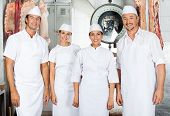 stock photo of slaughterhouse  - Team of confident butchers standing together in butchery - JPG