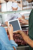 stock photo of slaughterhouse  - Cropped image of mature couple using digital tablet at butchery counter - JPG
