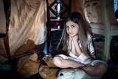 stock photo of creepy  - Portrait of scared little girl sitting on floor at creepy dark night   - JPG