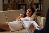 picture of psychologist  - Stressed young woman lying on the sofa in the office on psychologist - JPG