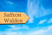 stock photo of saffron  - Wooden arrow sign pointing destination SAFFRON WALDEN ENGLAND against clear blue sky with copy space available - JPG