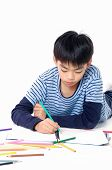 stock photo of schoolboys  - Portrait of a schoolboy lying down and writing in notebook - JPG