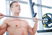 foto of work bench  - Concentrated young muscular man working out on bench press - JPG