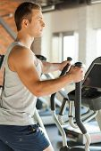 foto of cardio exercise  - Side view of handsome young man doing cardio exercise on step machine - JPG
