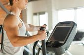 stock photo of cardio exercise  - Cropped image of handsome young man doing cardio exercise on step machine - JPG