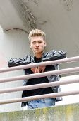 image of down jacket  - Attractive young man wearing black leather jacket looking down from balcony - JPG