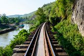 stock photo of train track  - Train track with river and mountain view railway in Thailand - JPG