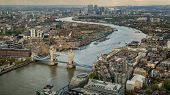 stock photo of bridge  - Overhead view of Tower Bridge and the skyline of London in England with the river Thames winding through the city - JPG