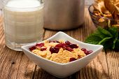 stock photo of milk glass  - Horizontal photo of white square bowl full of cornflakes with cranberries on wooden board - JPG