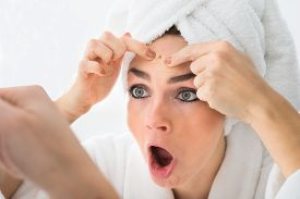 pic of forehead  - Shocked Woman Looking At Pimple On Forehead In Mirror - JPG