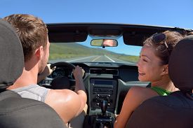 pic of steers  - Couple driving car on road trip travel vacation in convertible - JPG