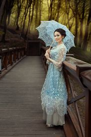 stock photo of fairies  - Woman standing on the bridge in the fairy forest - JPG