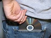 stock photo of shoplifting  - teen hiding cd in pocket - JPG