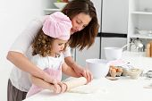 picture of mother child  - Mother and daughter using a rolling pin together in the kitchen - JPG