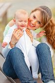Happy mother sitting on bench in park and holding smiling adorable baby girl in hands