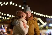 winter holidays and people concept - happy young couple dating and hugging in christmas evening outd poster