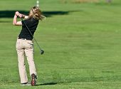 foto of ladies golf  - Lady golfer getting ready to chip to the green from the rough - JPG