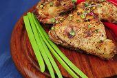 Постер, плакат: мясопродуктов: Жареные куриные ножки украшенный с ручки зелёный лук и перец на деревянной тарелке над bl