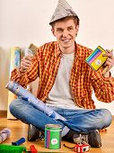 Repair home man holding paint roller for wallpaper. Male in newspaper cap renovation apartment. Pain poster