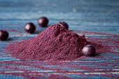 Heap of acai powder and berries on wooden background poster