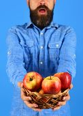 Farmer With Surprise On Face Holds Red Apples, Close Up. poster