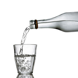 stock photo of bottle water  - water poured from the bottle to the glass  - JPG