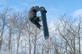 A Snowboarder Performs A Mid-air Grab In A Terrain Park poster
