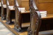 stock photo of pews  - Detail of the church seats with Bibles - JPG