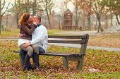 Young couple kissing while sitting on the bench in the park on cloudy autumn day